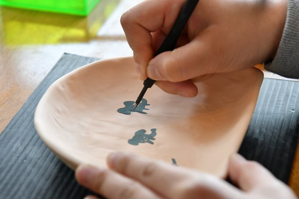 Somebody is painting on a raw piece of ceramic