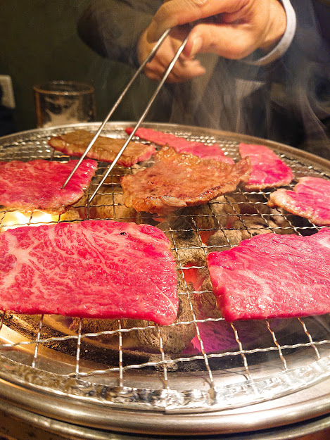 Raw and grilled beef on a barbequeue stove