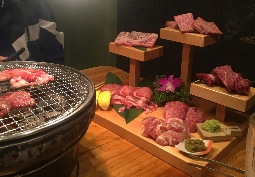 A choice selection of various kinds of meat next to a BBQ grill