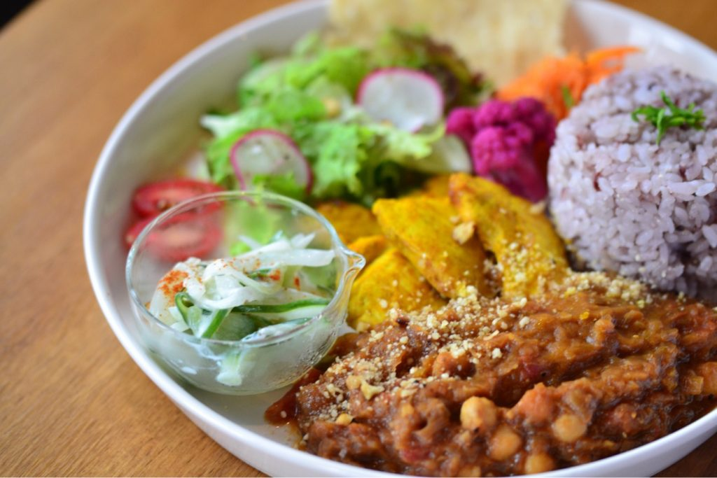 Gluten-free fresh curry made from chick peas and tomatoes, spicy chicken, rice and salad with pickles on the side.